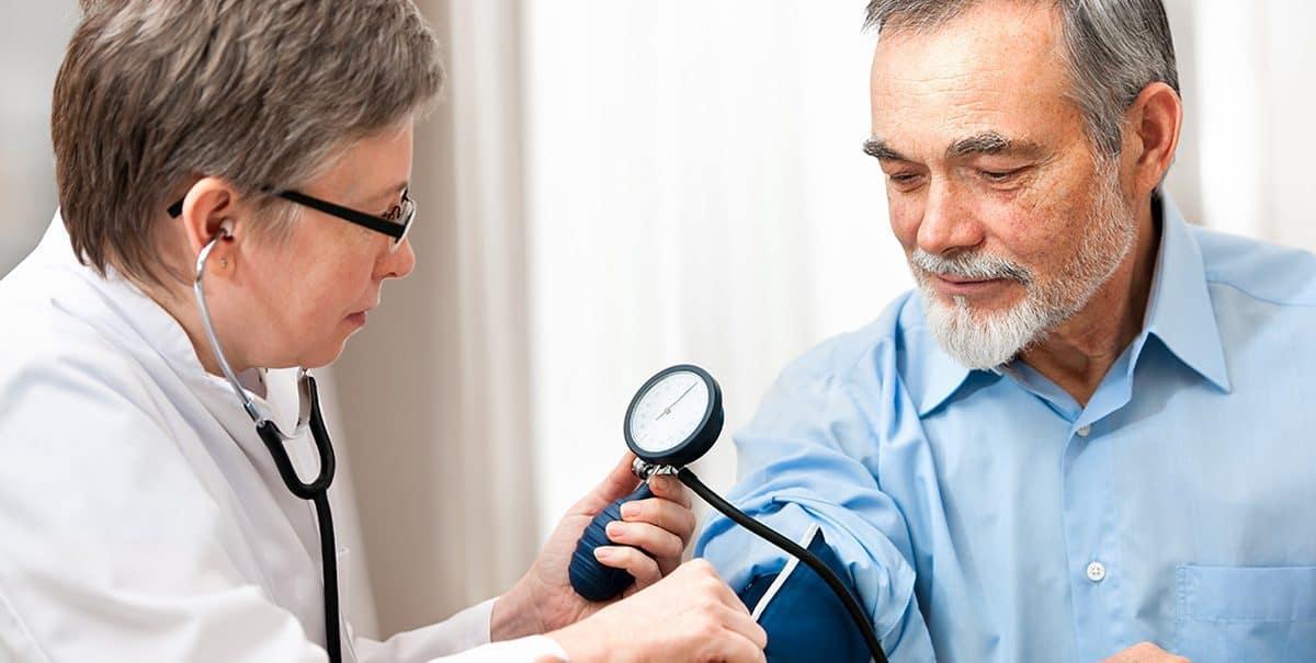 доктор измеряет давление у мужчины
