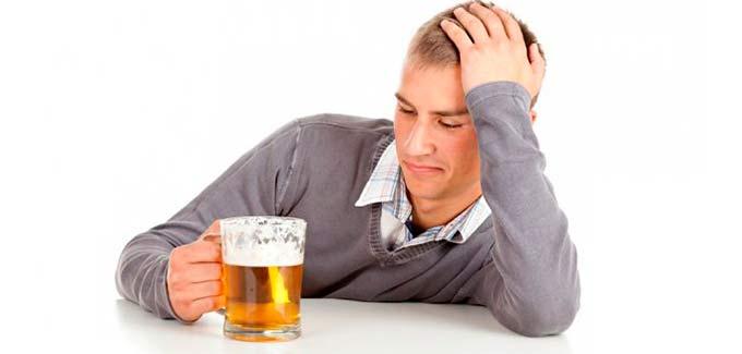 мужчина смотрит на бокал пива