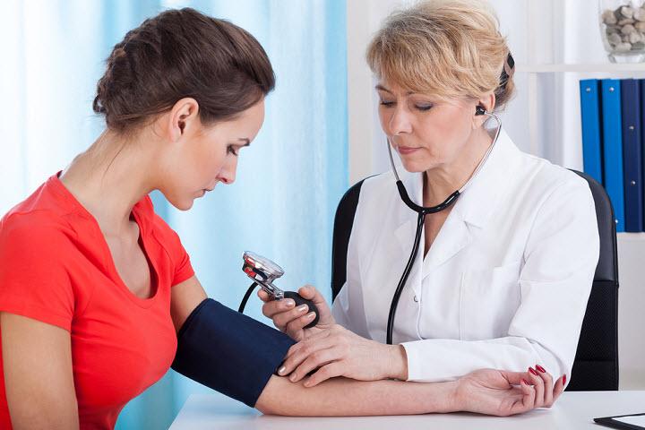 врач измеряет девушке давление
