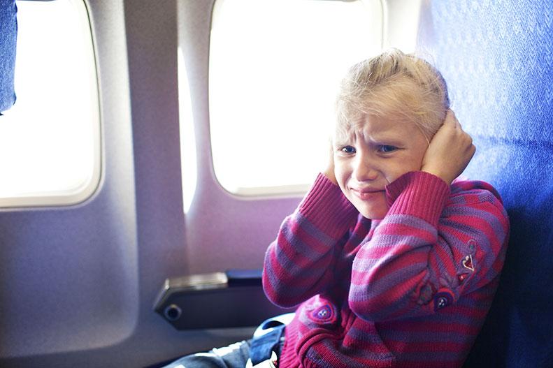 девочка в самолете держится за уши