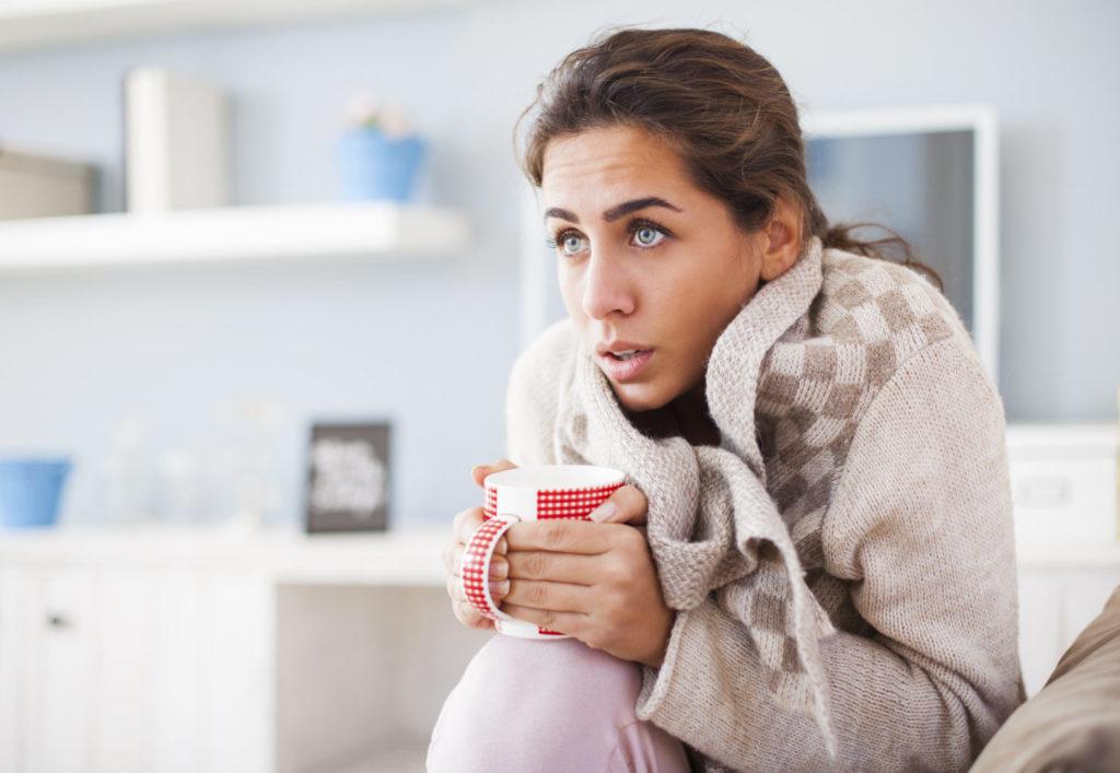 девушка с кружкой чая в теплой одежде