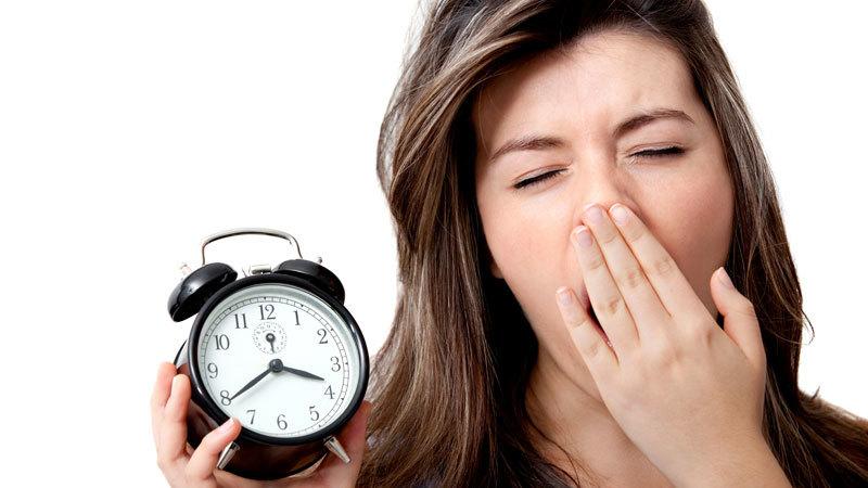 женщина с будильником зевает