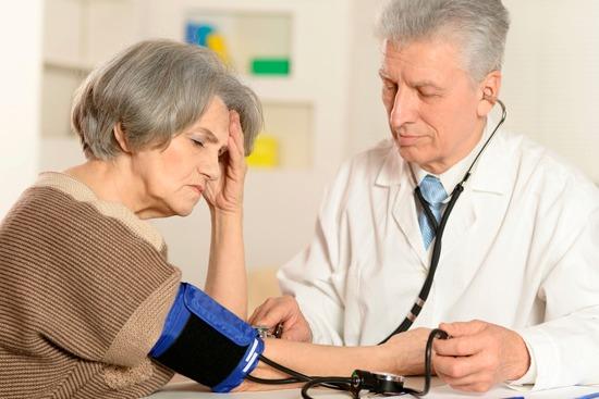 врач измеряет женщине давление