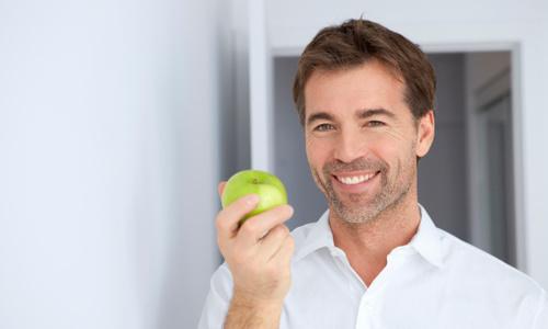 мужчина улыбается и держит яблоко