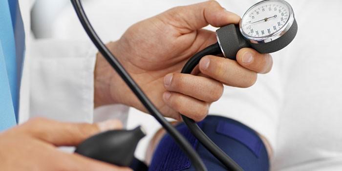 врач держит в руке тонометр