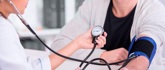 врач измеряет давление мужчине