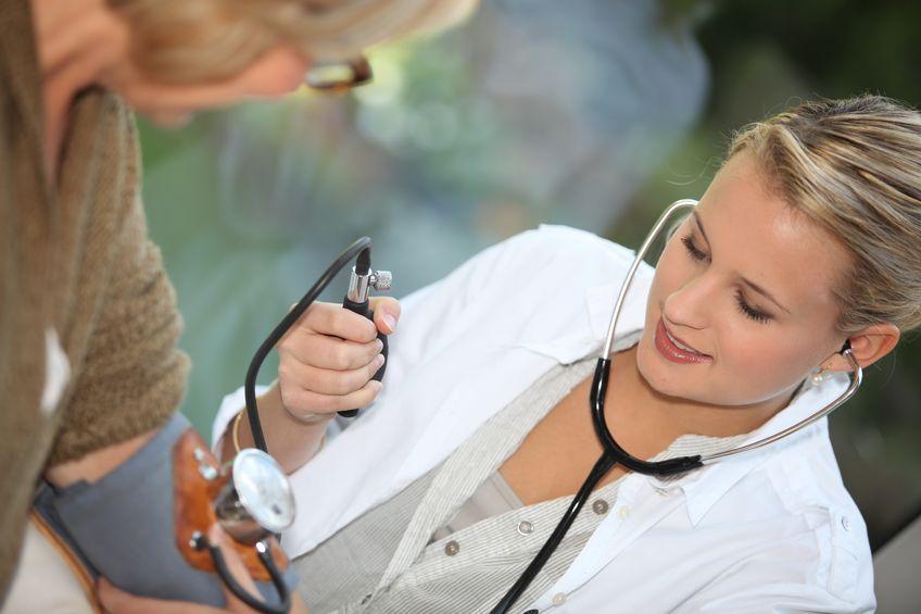 доктор измеряет женщине давление