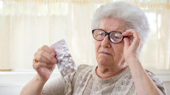 пожилая женщина смотрит на таблетки