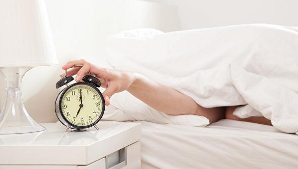 рука выключает будильник
