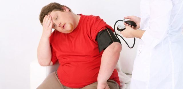 доктор измеряет мужчине давление