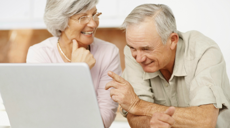 пожилая пара смотрит в компьютер