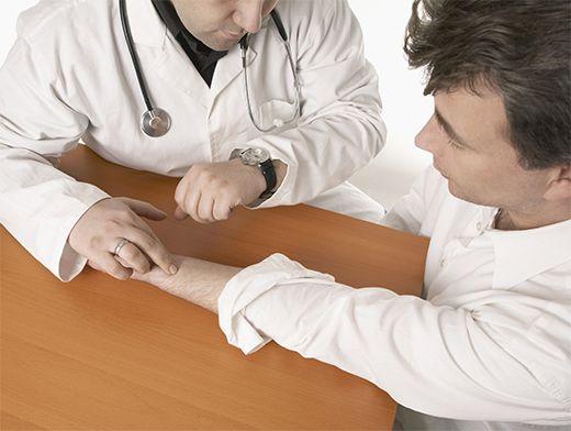врач измеряет пульс мужчине
